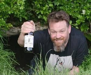 Richard Siberry holding a bottle at the entrance to the Cave of Oweynagat